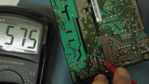 pomiar napięcia na układzie sterującym zasilacza z miernikiem wskazującym wartość 575