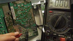 zasilacz monitora oraz miernik pokazujący wartość zero